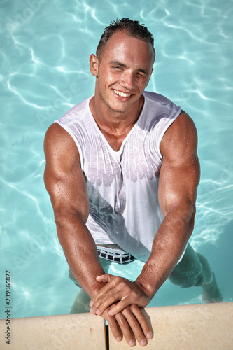 0909103be9 Muscular young sexy wet man in swimming trunks and white tank top posing in outdoor  pool