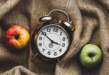 Apples and alarm clock on jute sack background. Autumn season harvest