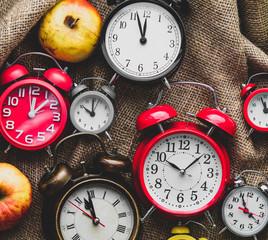 Apples and alarm clocks on jute sack background. Autumn season harvest