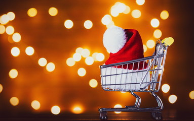 Santa Claus hat in shopping cart and Christmas Lights on background