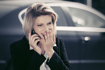 Fashion business woman calling on cell phone next to her car