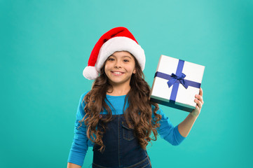 New year party. Santa claus kid. Little girl child in santa hat. Present for Xmas. Childhood. Happy winter holidays. Small girl. Christmas shopping. For Santa. blue background.