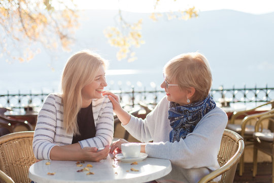 Conversation of two beautiful women in street cafe. Mother and her adult daughter have dialogue outdoor. Happy senior woman and young girl are smiling. Concept of support, care, family love, relations