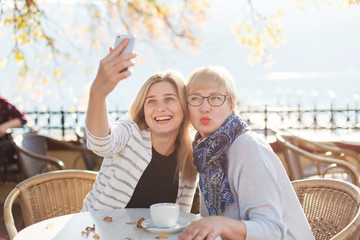 Two funny beautiful women take selfie. Mother and her adult daughter have meeting in autumn street cafe outdoor. Happy senior woman and young girl are smiling and using mobile phone.