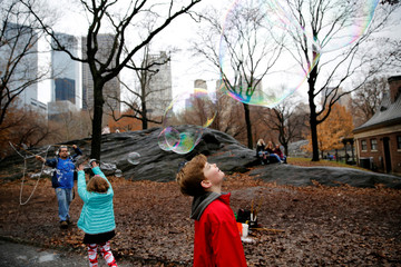 Children play as a man blows bubbles at Central Park in New York