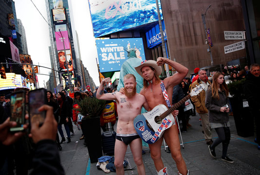 A man poses with the Naked Cowboy in New York