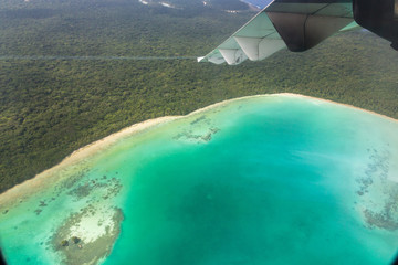 A view of azure lagoon and yellow sandy beach from a regional turboprop/propeller airplane window while arriving/departing Isle of Pines (L'Ile-des-Pins). Flying over New Caledonia, Melanesia, Oceania