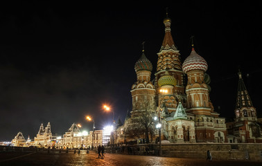 People walk in front of St. Basil's Cathedral, with GUM department store in the background decorated with lights for the New Year and Christmas season in Moscow