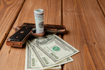 Stack of Money, drugsand a gun on a wooden table, concept about danger and threat of the drug