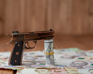 Gun and Stack of Money lying on the hryvnia on a wooden table. Drug use, crime, addiction and substance abuse concept on wooden background