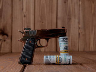 Robbery concept. Gun with money on wooden background