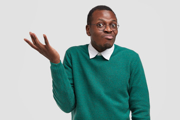 Funny dark skinned man cannot understand what girlfriend wants from him, raises hand in bewilderment, has confused facial expression, isolated over white background. Unaware guy models indoor