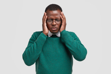 Desperate black young man keeps both hands on head, closes eyes, suffers from migraine, has sad fatigue facial expression, wears elegant sweater, isolated over white background. Negative feeling