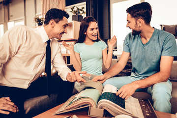 Young Couple Consulting With Furniture Seller.