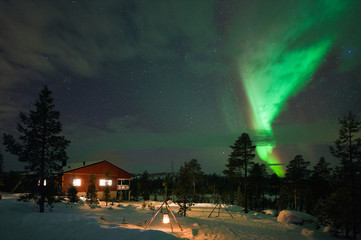 Winter night with Aurora Borealis; Northern Lights,  above country house.