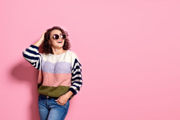 Happy beautiful girl with amazing toothy smile posing in fashionable sweater, jeans and sunglasses. Young girl standing on pink pastel background.