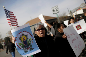 A woman holds a picture of Jakelin Caal, a 7-year-old Guatemalan girl who died in U.S. custody after crossing illegally from Mexico to the U.S., during a protest held to demand justice for her in El Paso
