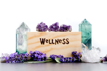 Wellness - word burnt in wood with purple lavender flowers, amethyst, fluorite and quartz crystals on slate with white background