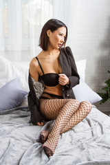 Young girl in lace lingerie sitting on the bed in the bedroom