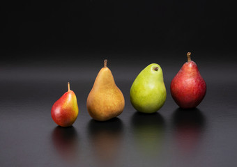 Healthy and nutritious snacks.  Delicious fresh pears on a black background.  Forelle, Bosc, D'Anjou, Starkrimson Red Pears variety.