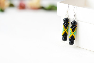 Handmade beaded earrings in style of jamaican flag close up