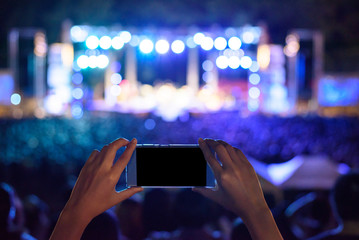 Hand holding smartphone photographing live concert , People taking photographs with smart phone during a music entertainment event