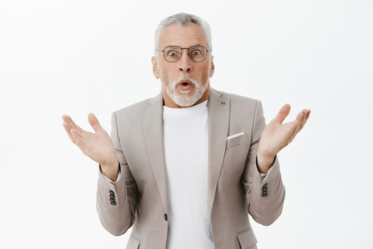 Waist-up shot of shocked and stunned old man raising hands in surprise folding lips and gasping popping eyes confused and questionned cannot undertand what happening posing in suit and glasses