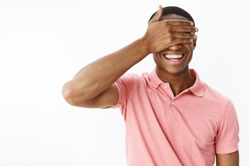 Charismatic funny and happy attractive african american man closing eyes with palm not to peek smiling joyfully anticipating surprise or gift, waiting patient and delighted over gray background