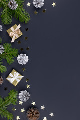 Festive Christmas background with fir branches, presents, decorations on black, copy space
