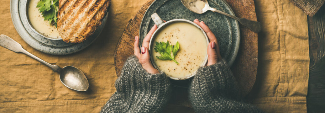 Autumn, Winter home dinner. Flat-lay of Fall warming celery cream soup, grilled bread and female hands over linen tablecloth, top view, wide composition. Comfort food, healthy and slow food concept