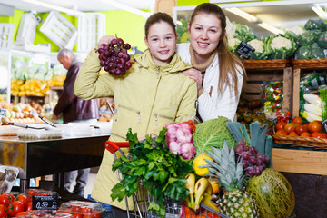 Girl with mother choosing fruits in store