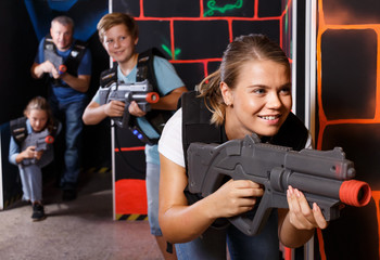 Happy young girl with laser gun  during laser tag game with  players