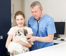 Happy girl with dog consulting by veterinarian