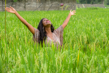 young beautiful and happy black African American woman in cool dress having fun at tropical rice field enjoying exotic holidays trip in Asia exploring traditional village