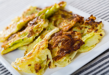 Photography of plate with cabbage leaves in batter