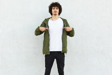 Photo of curly man points at white t shirt, shows free space for your advertisement, logo or promotional content, poses over concrete wall, advertises new outfit. People, clothes, design concept