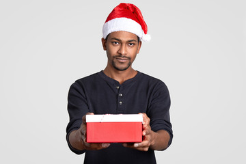 Isolated shot of serious black man wears Santa Claus headgear, carries little box of present, dressed in black jumper, poses over white studio wall. People, winter holidays and celebration concept