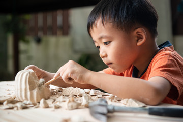 A young boy digging educational fossil in the garden