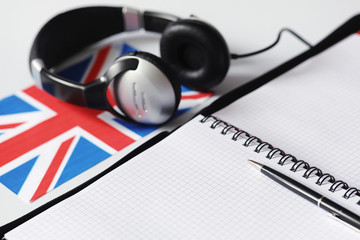 Learning foreign languages. Notepad for entries and a flag. Language courses, audio audition