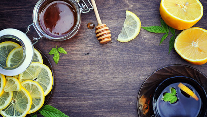 Honey and lemon. Honey stick and slices of sliced lemon on a wooden table. Tea in a cup and sweet lime honey in a jar.