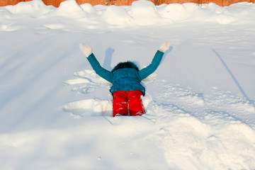 A girl in a sea-green color jacket and orange bolognese sports pants is lying on white freshly fallen deep snow and waving her arms, making butterfly wings with her handprints on the snow.