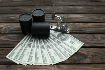 barrels of oil, oil refining, dollars on a wooden background. the market for the sale and purchase of petroleum and petroleum products.