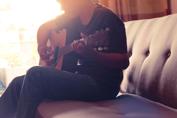 man playing guitar on  sofa and sun light background