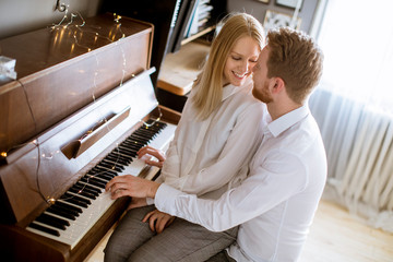 Loving young couple playing piano