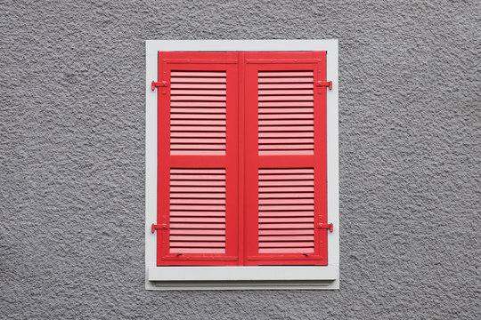 Closed red wooden window shutters against grey wall