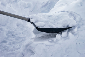 People cleans snow shovel on the street, close-up
