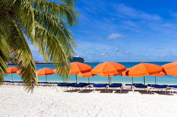 beach chairs and  red umbrellas on caribbean island St. Maarten