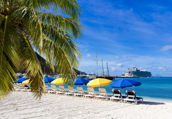 beach chairs and  colorful umbrellas on caribbean island St. Maarten