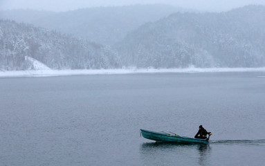 A man travels on a boat with a small motor across the Yenisei river during snowfall outside Krasnoyarsk