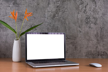 Blank screen of laptop computer and mouse with flowers vase on raw concrete background